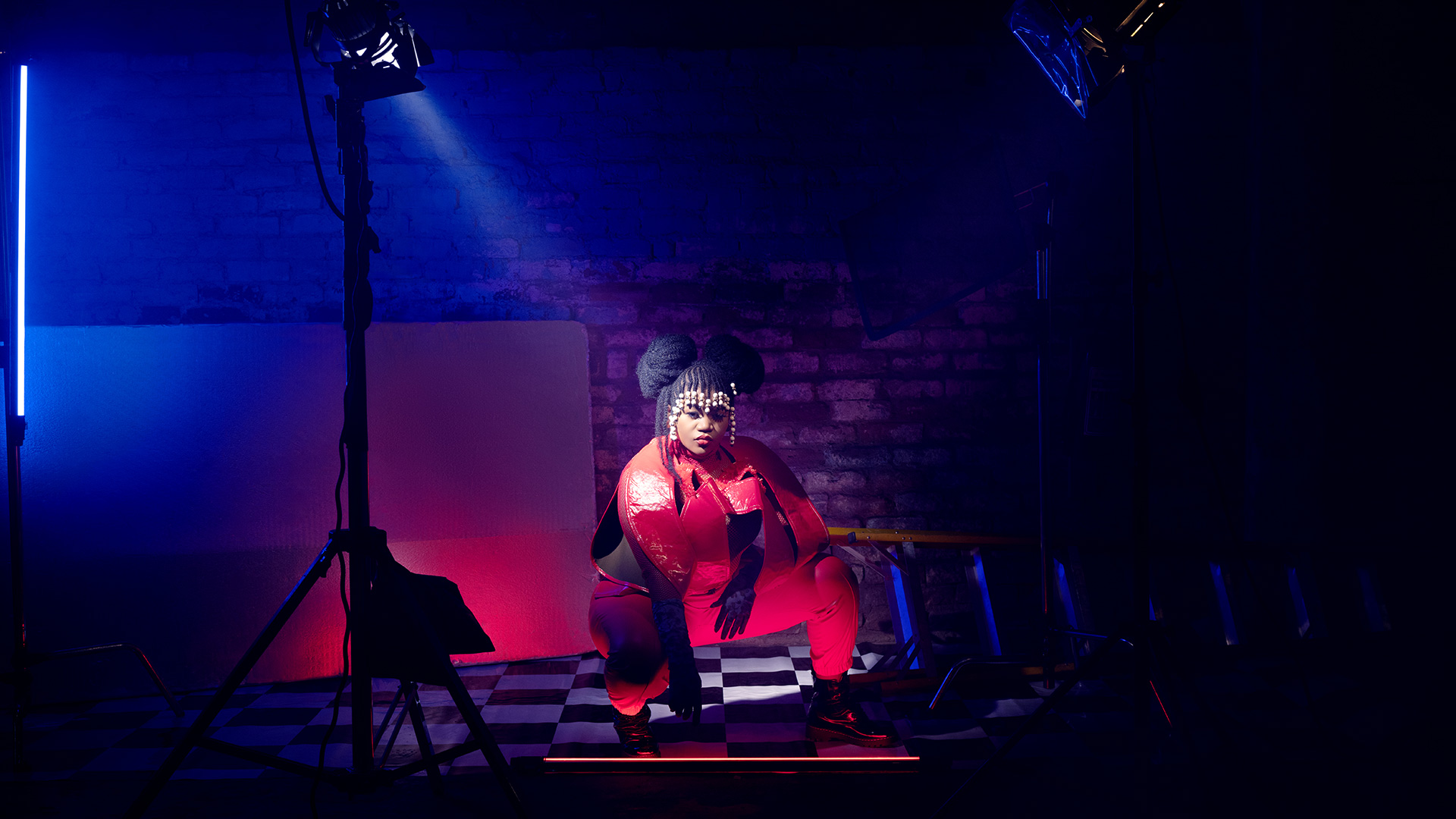 Busiswa crouching between two spotlights, dressed in red